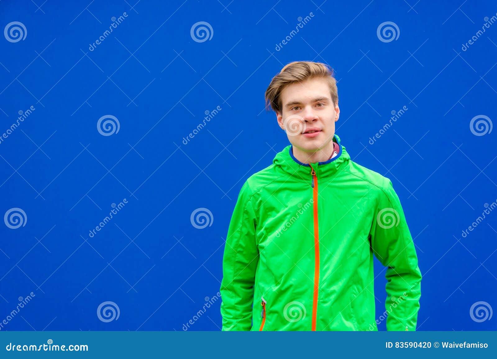 Muchacho adolescente que mira en cámara sobre el fondo del contraste al aire libre