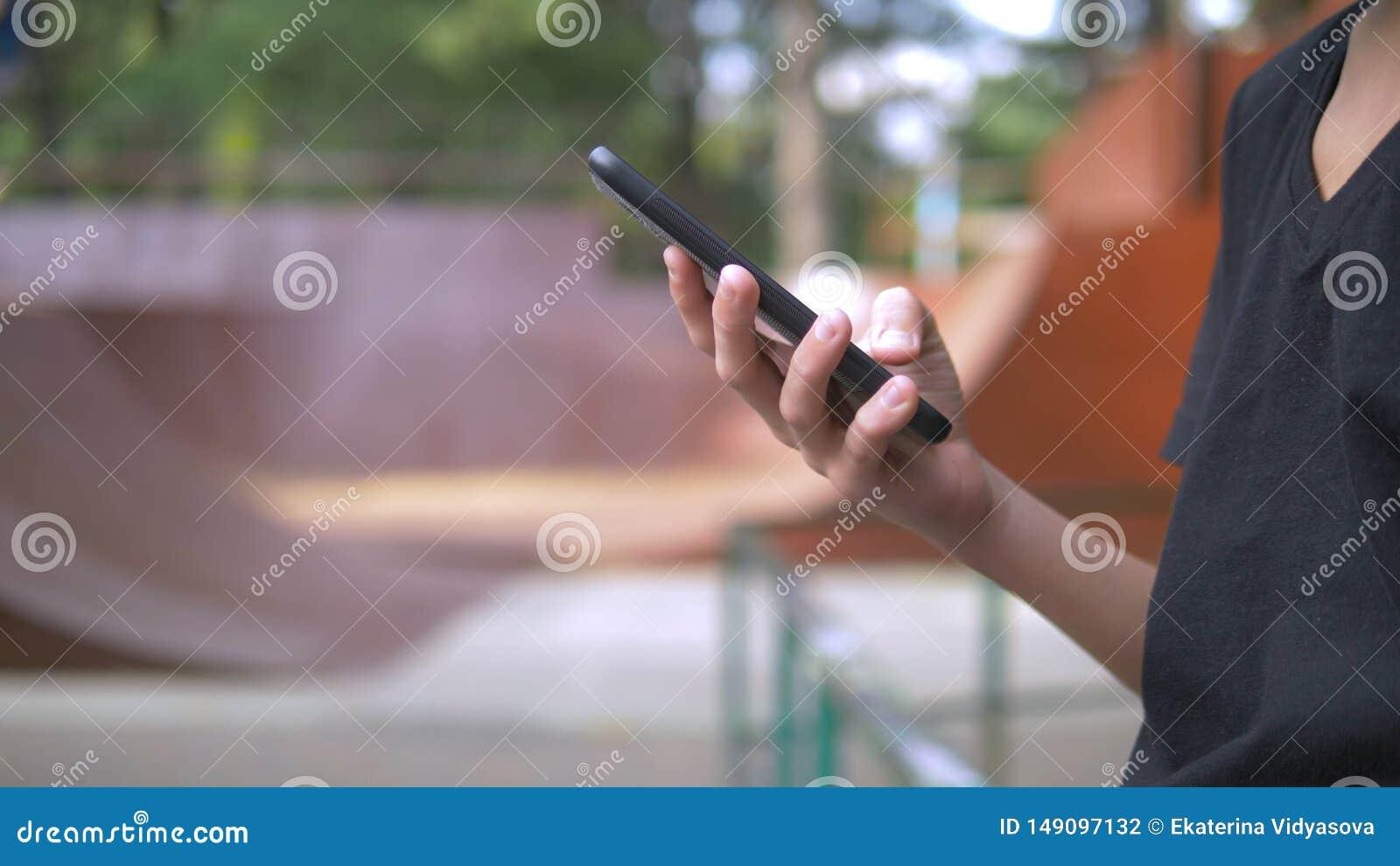 Muchacho adolescente solamente usando un tel?fono m?vil contra la perspectiva de un parque del pat?n mientras que otros ni?os se