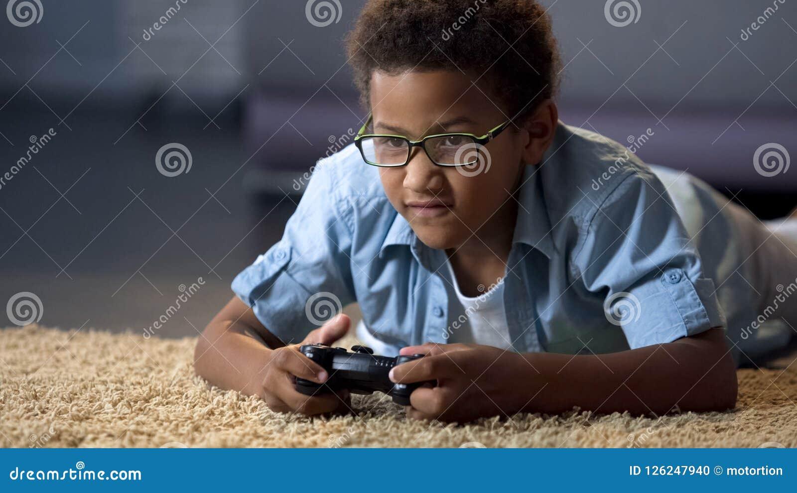 Muchacho afroamericano absorbedly que juega en la nueva consola del videojuego, actividad casera