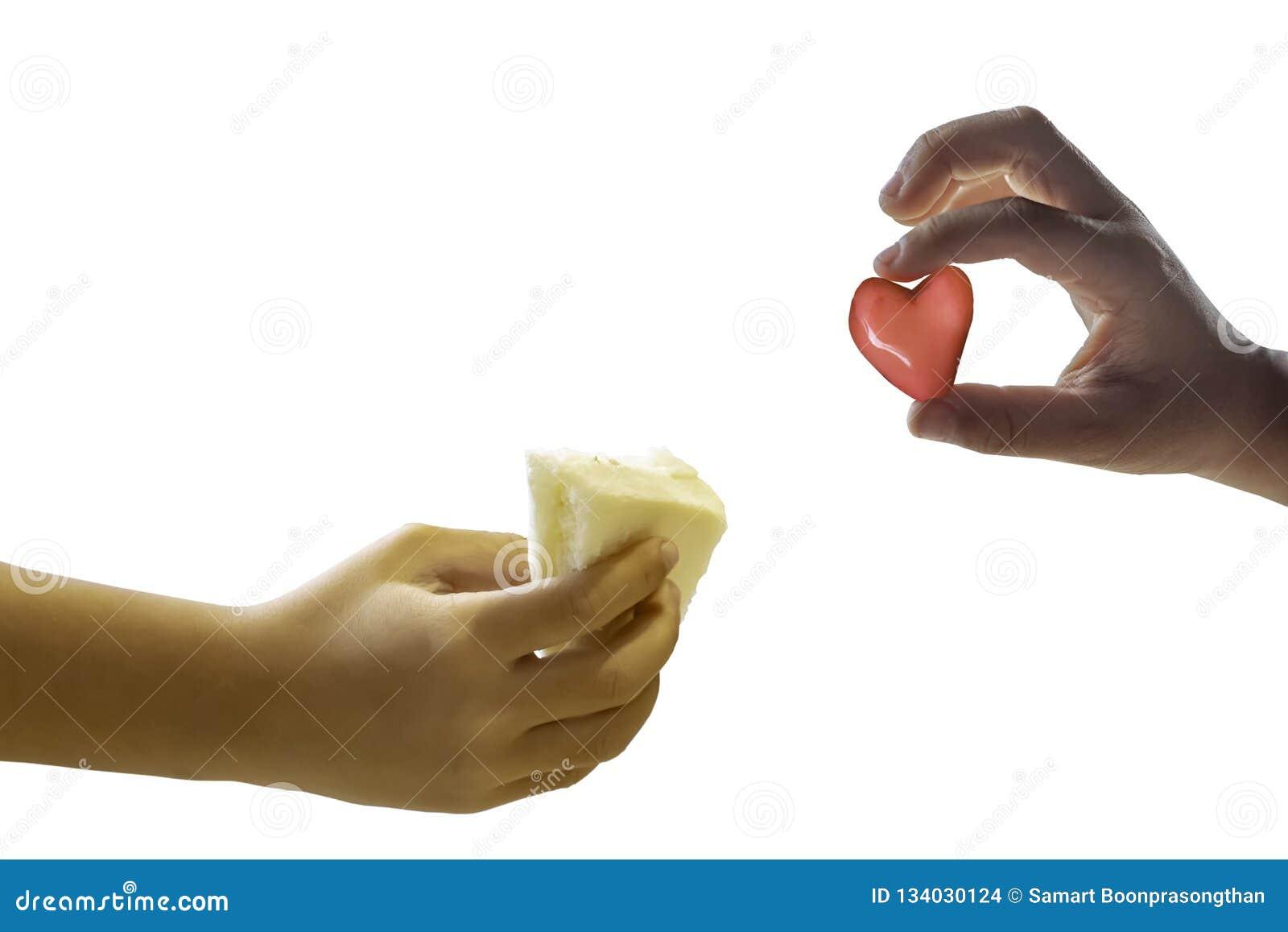 Muchacho aislado de la mano que sostiene el bocadillo del pan y que lleva a cabo un corazón rojo de la forma del caramelo en un f
