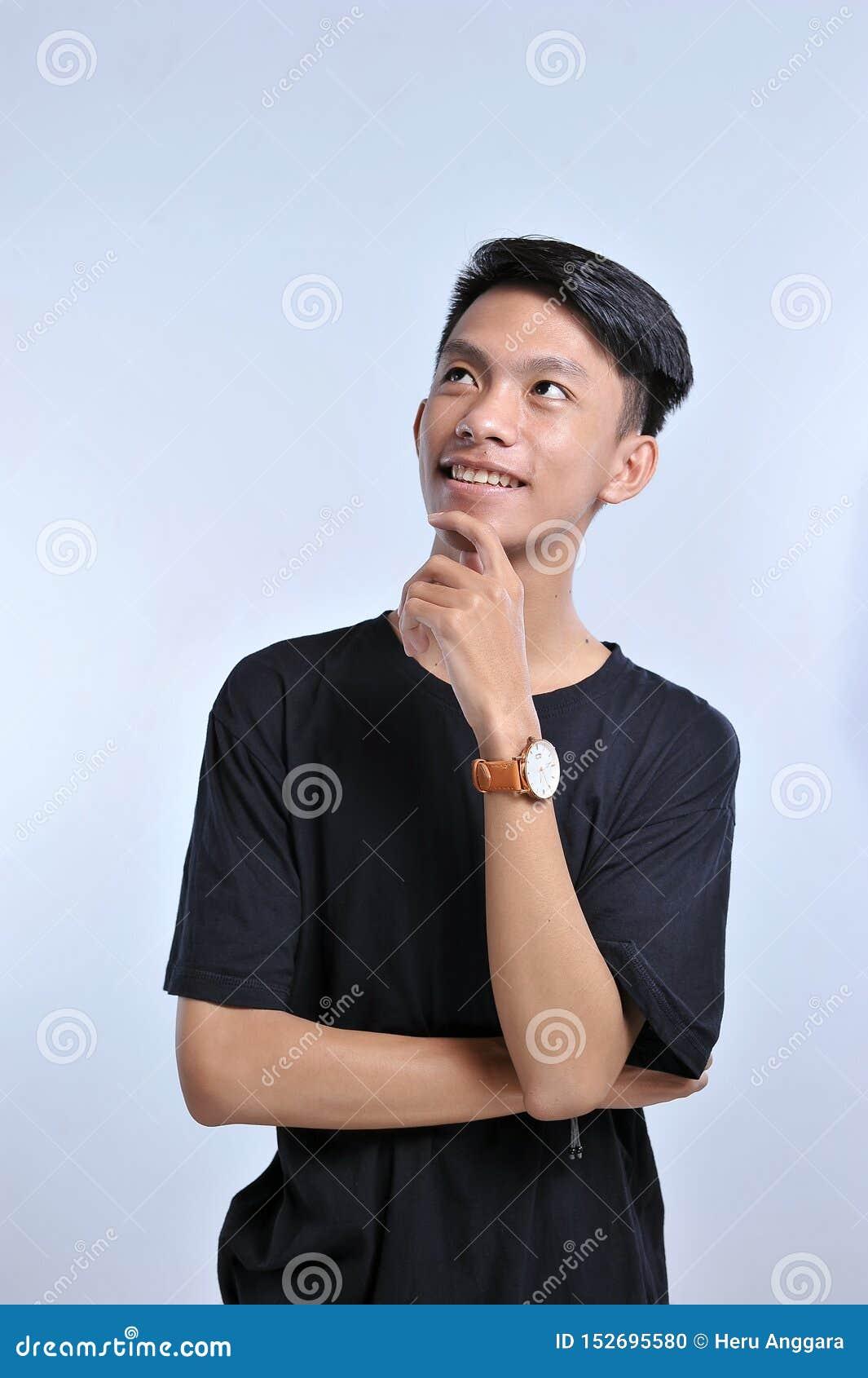 Muchacho asiático joven hermoso que lleva la camiseta y el reloj negros con la mano en la barbilla que piensa en la pregunta, exp