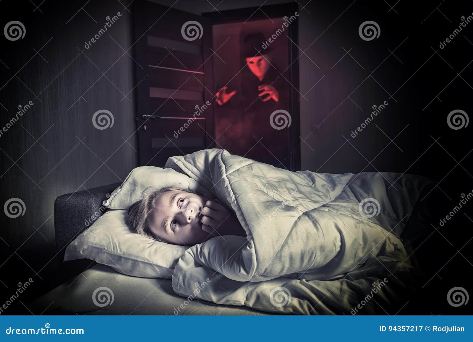 Muchacho asustado que miente en la cama mientras que el extranjero enmascarado