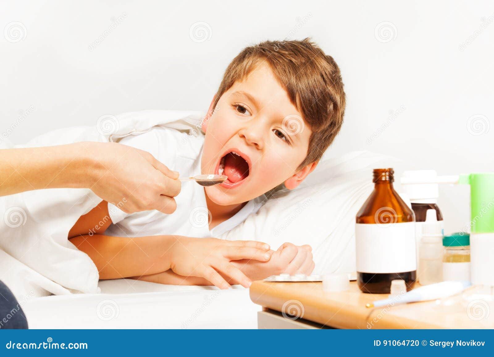Muchacho caucásico enfermo del niño que toma los meds que ponen en cama