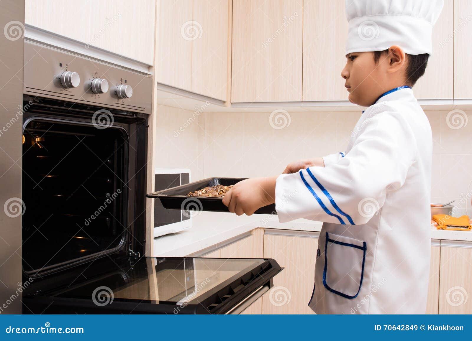 Muchacho chino asiático en las galletas blancas de la hornada del uniforme del cocinero