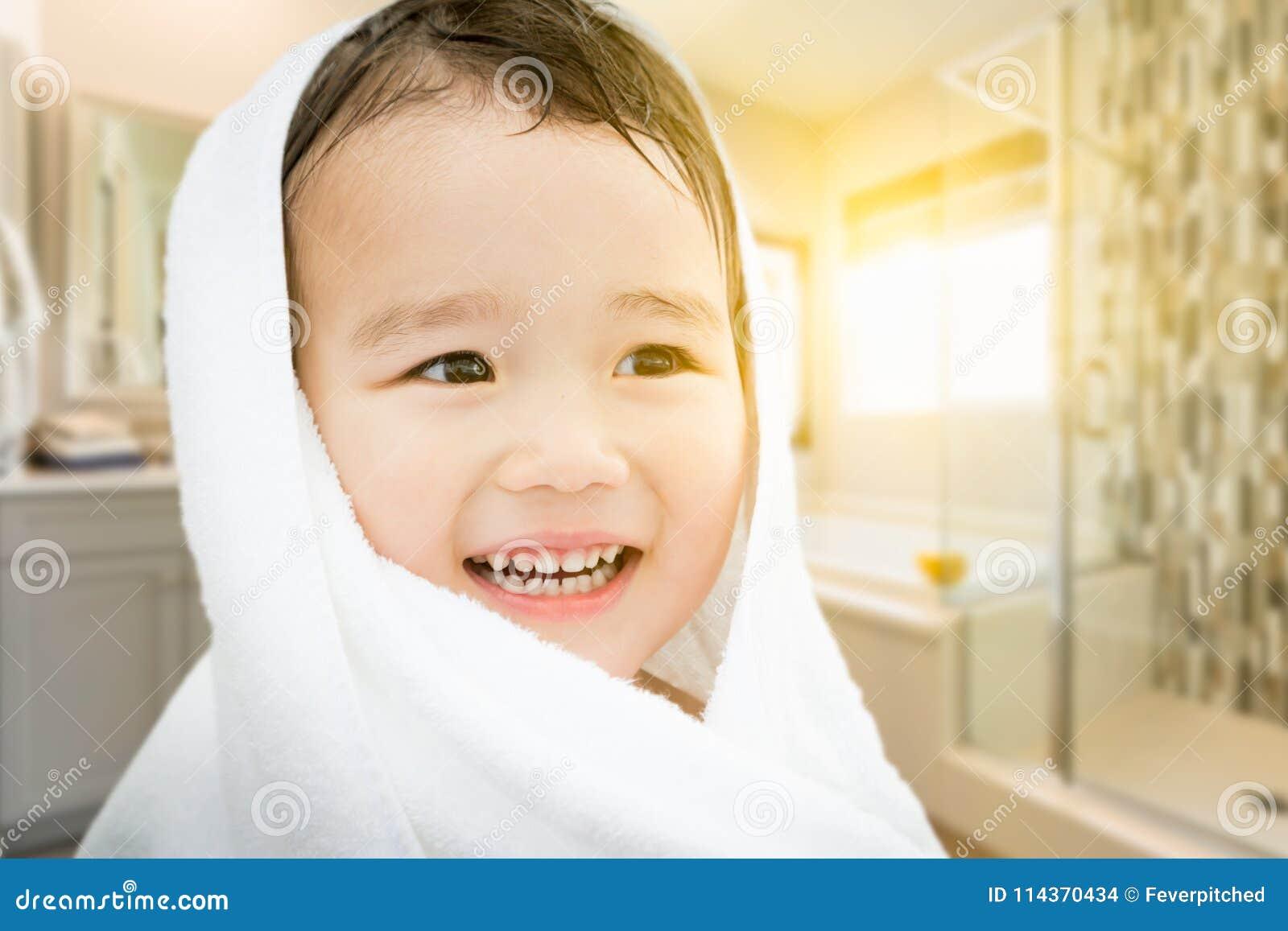 Muchacho chino y caucásico de la raza mixta linda feliz en abrigo del cuarto de baño