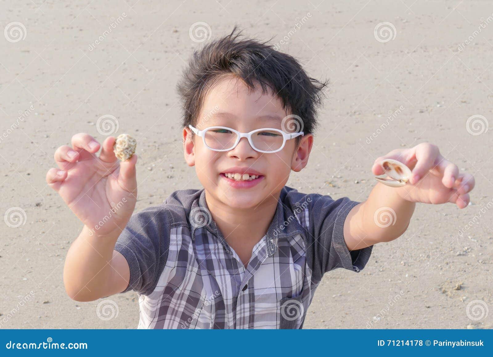 Muchacho con la cáscara en la playa