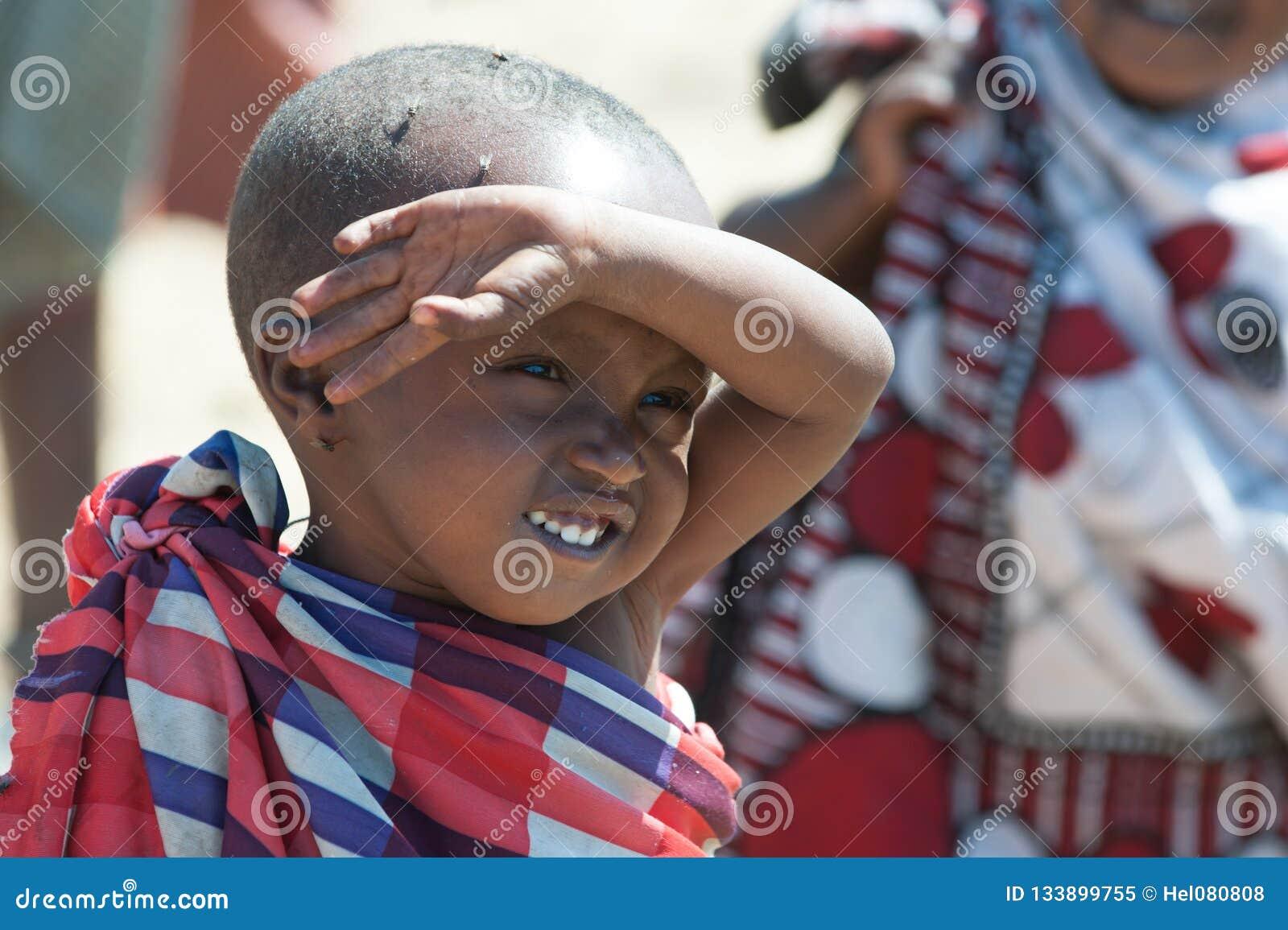 Muchacho con los ojos llenos de moscas, Tanzania de Maasai Las moscas ponen los huevos en ojos de modo que el niño pudiera ir cie