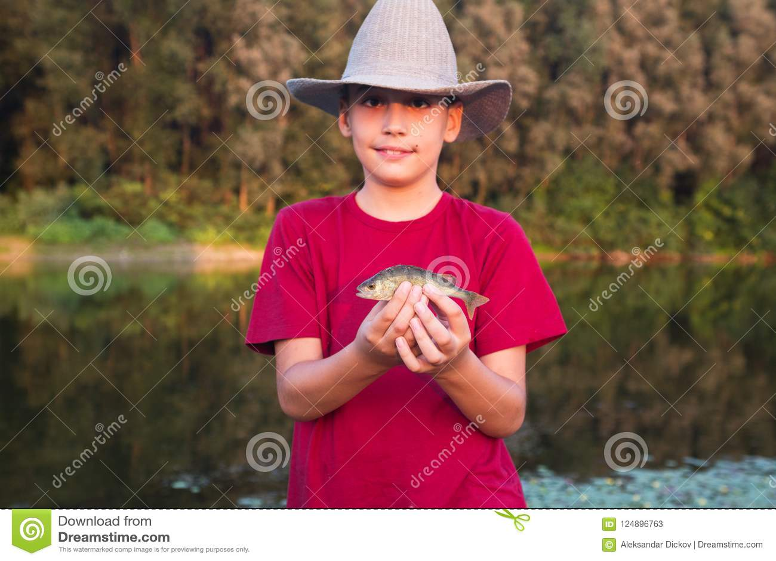 Muchacho con su primera captura de la perca