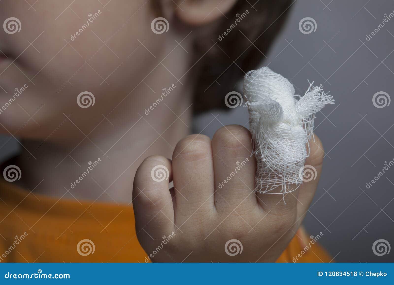 Muchacho con una herida vendada en su finger