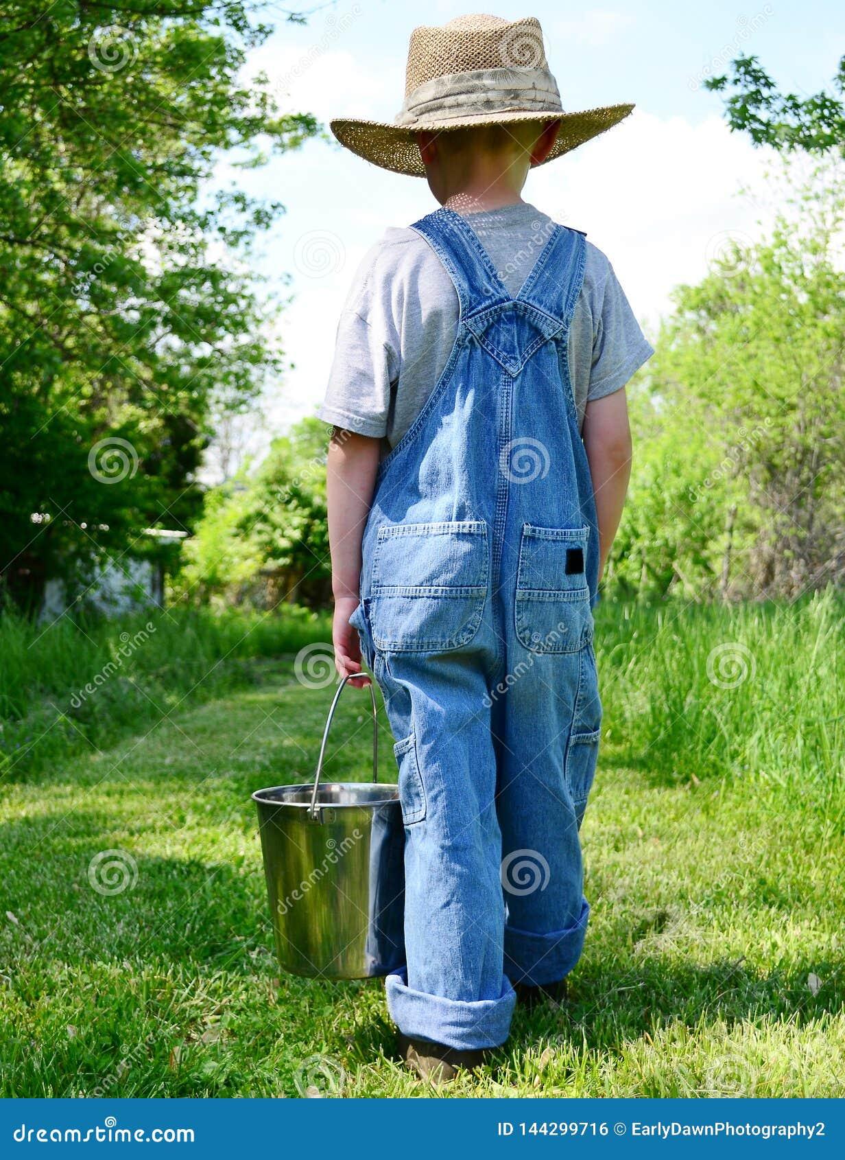 Muchacho de granja con el cubo de ordeño