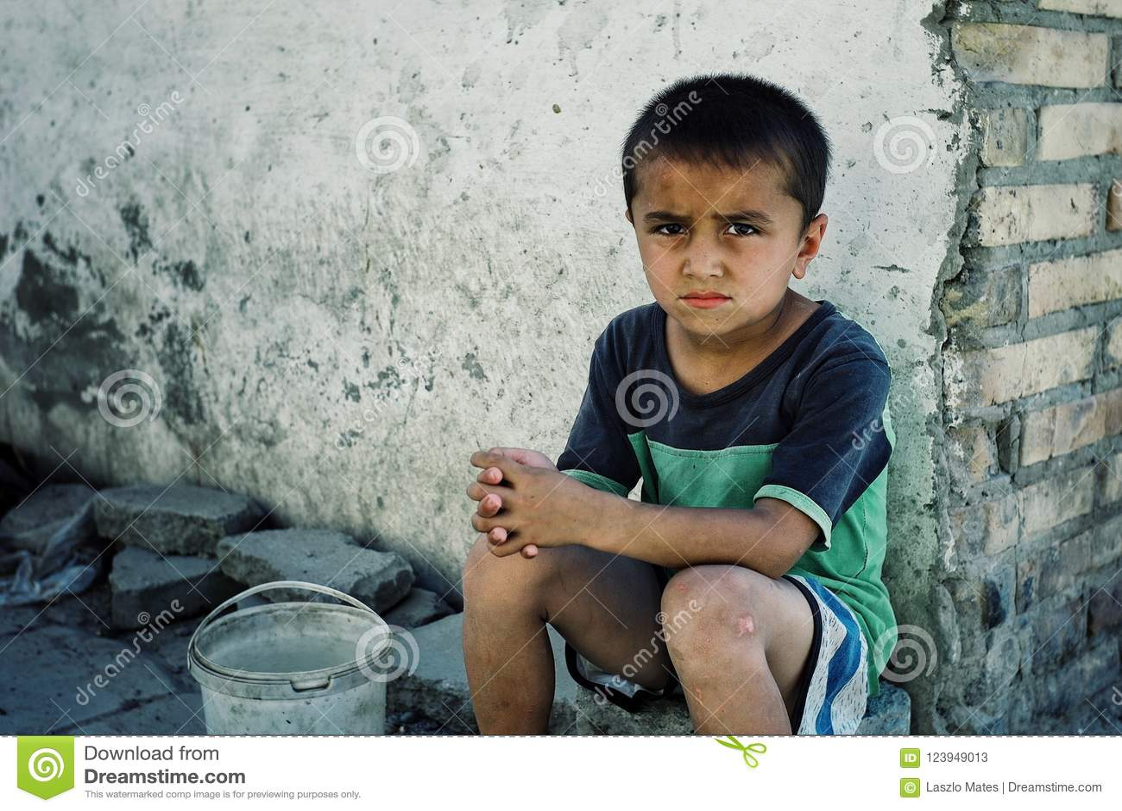 Muchacho de mirada triste joven que espera en una esquina de calle para recoger un poco de agua de la reserva de comunidad