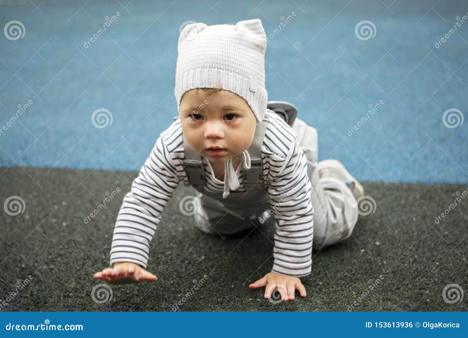 Muchacho del bebé en arrastres grises en el patio Ni?o en todos los fours