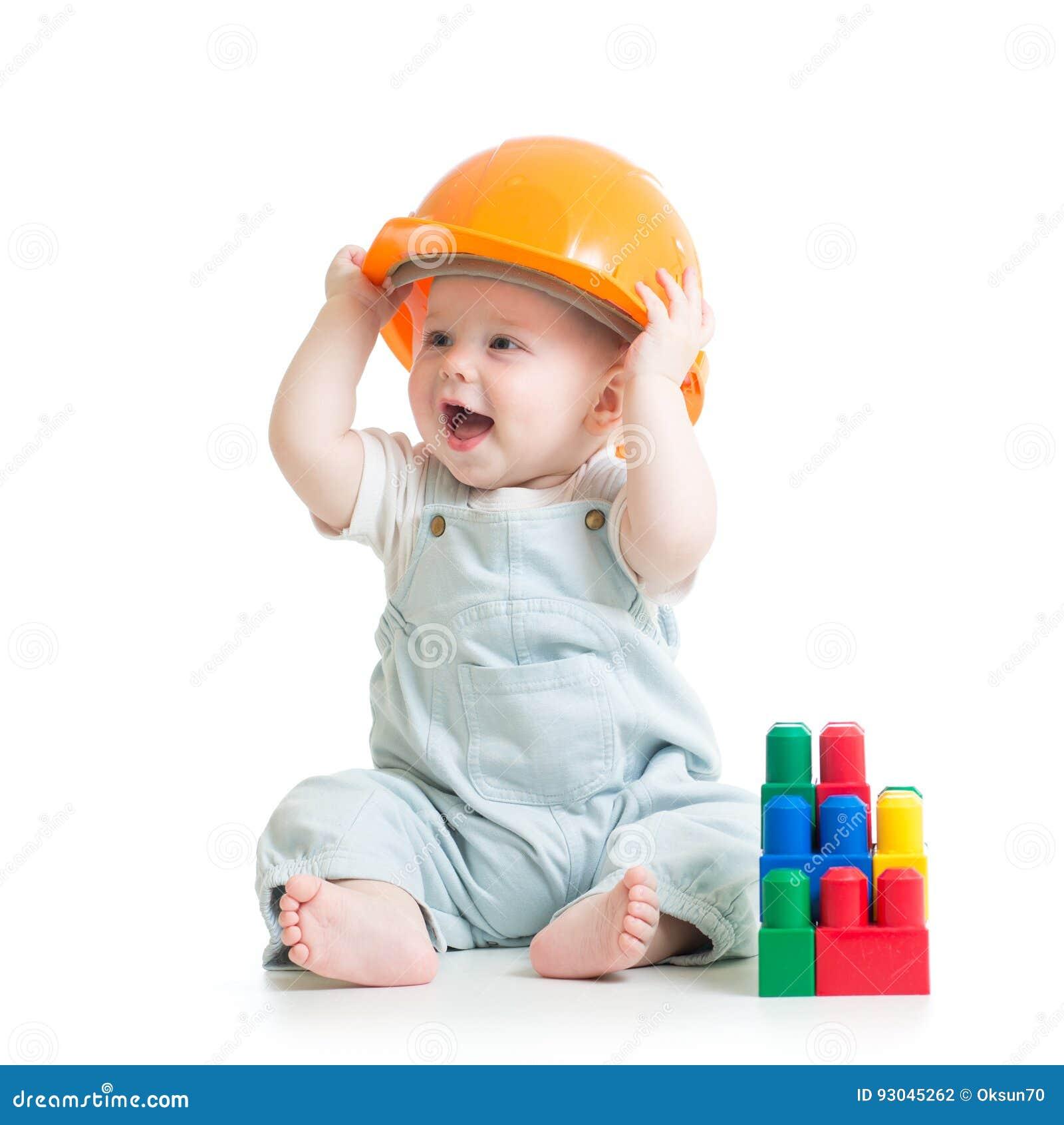 Muchacho del cabrito que juega con el juguete de los bloques huecos