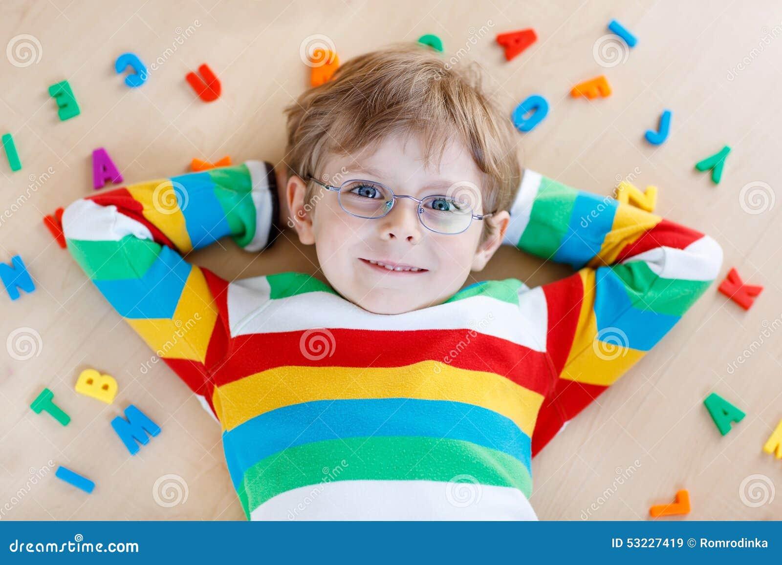 Muchacho del niño con las letras coloridas, interiores