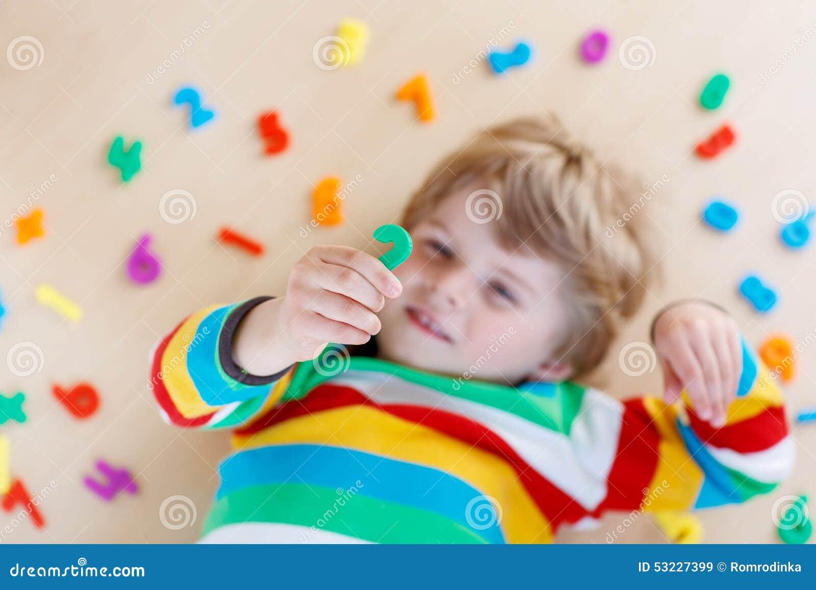Muchacho del niño con los números coloridos, interiores