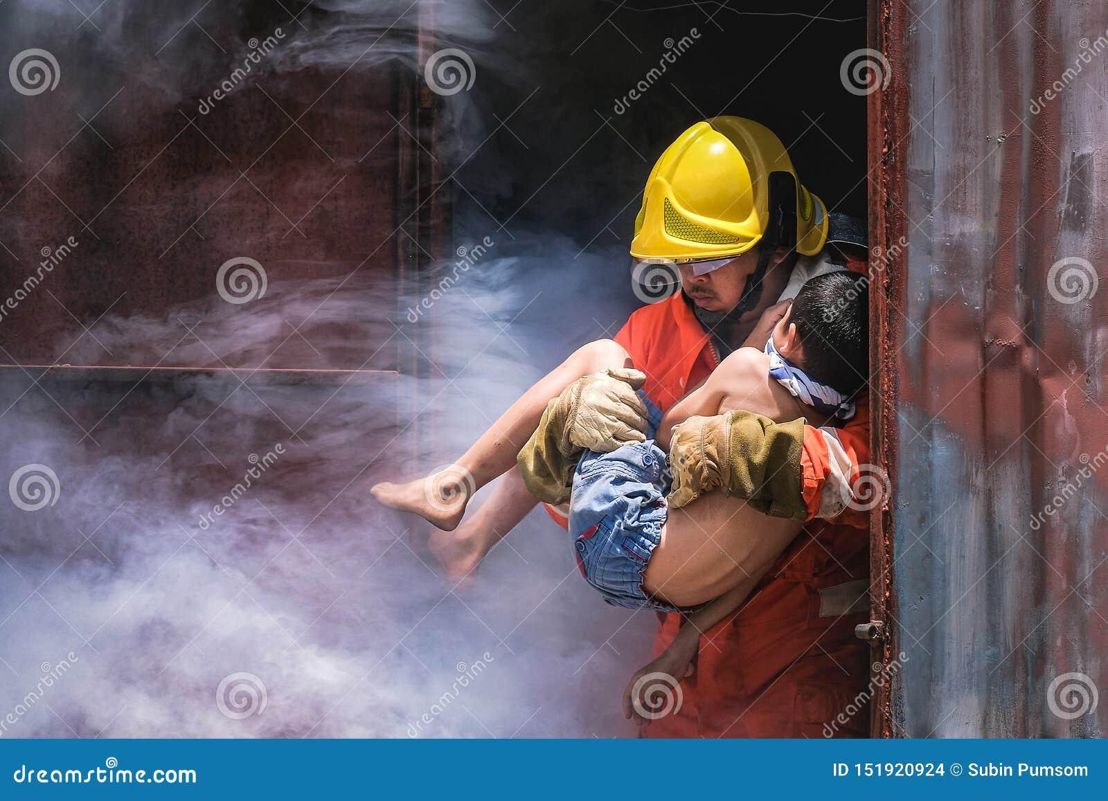 Muchacho del niño de la tenencia del bombero para ahorrarlo en bomberos del fuego y del humo para rescatar a los muchachos