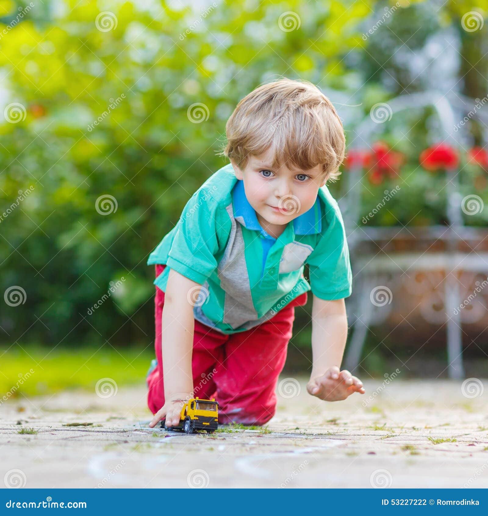 Muchacho del niño que juega con el juguete del coche, al aire libre