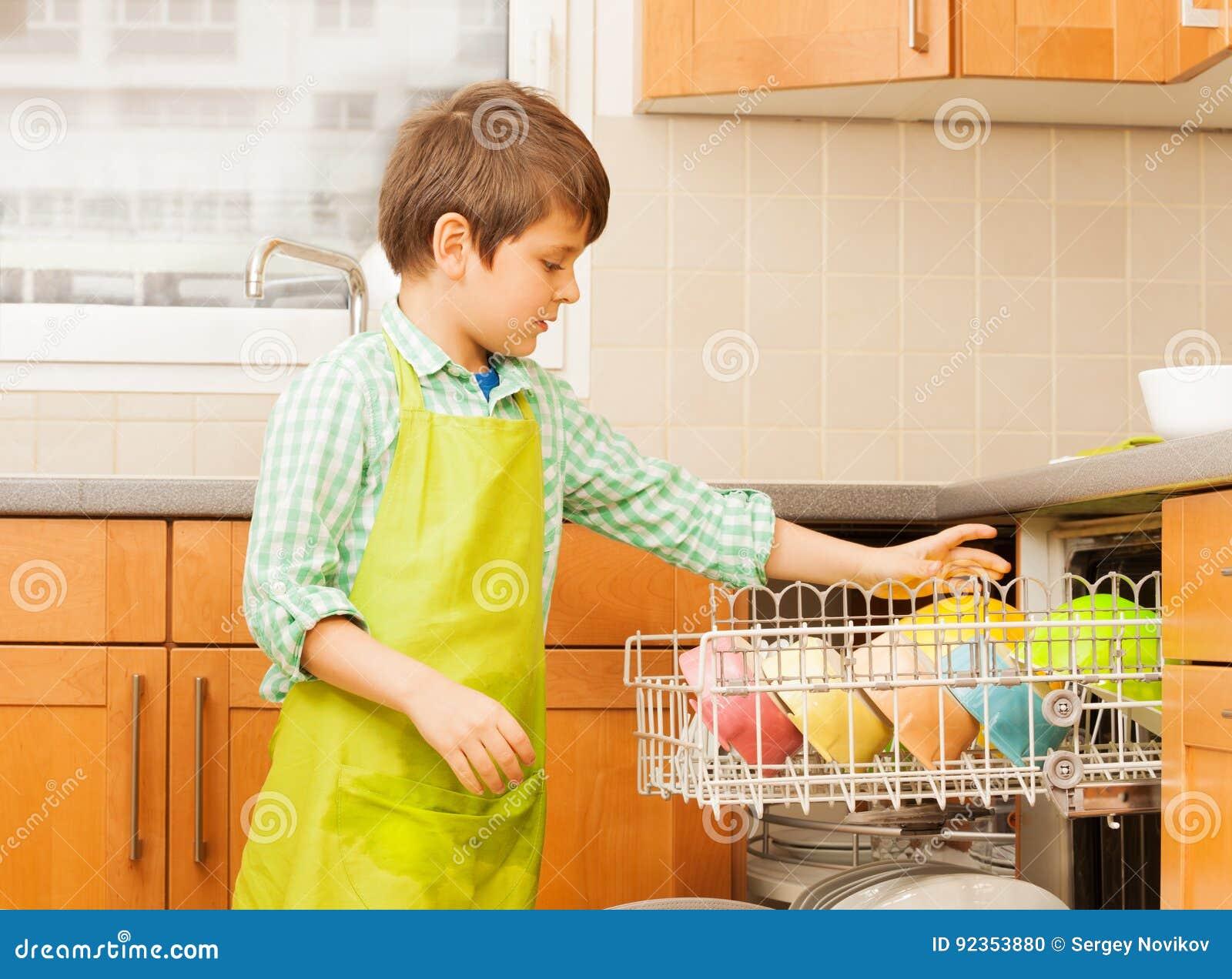Muchacho del niño que sale de la loza limpia del lavaplatos