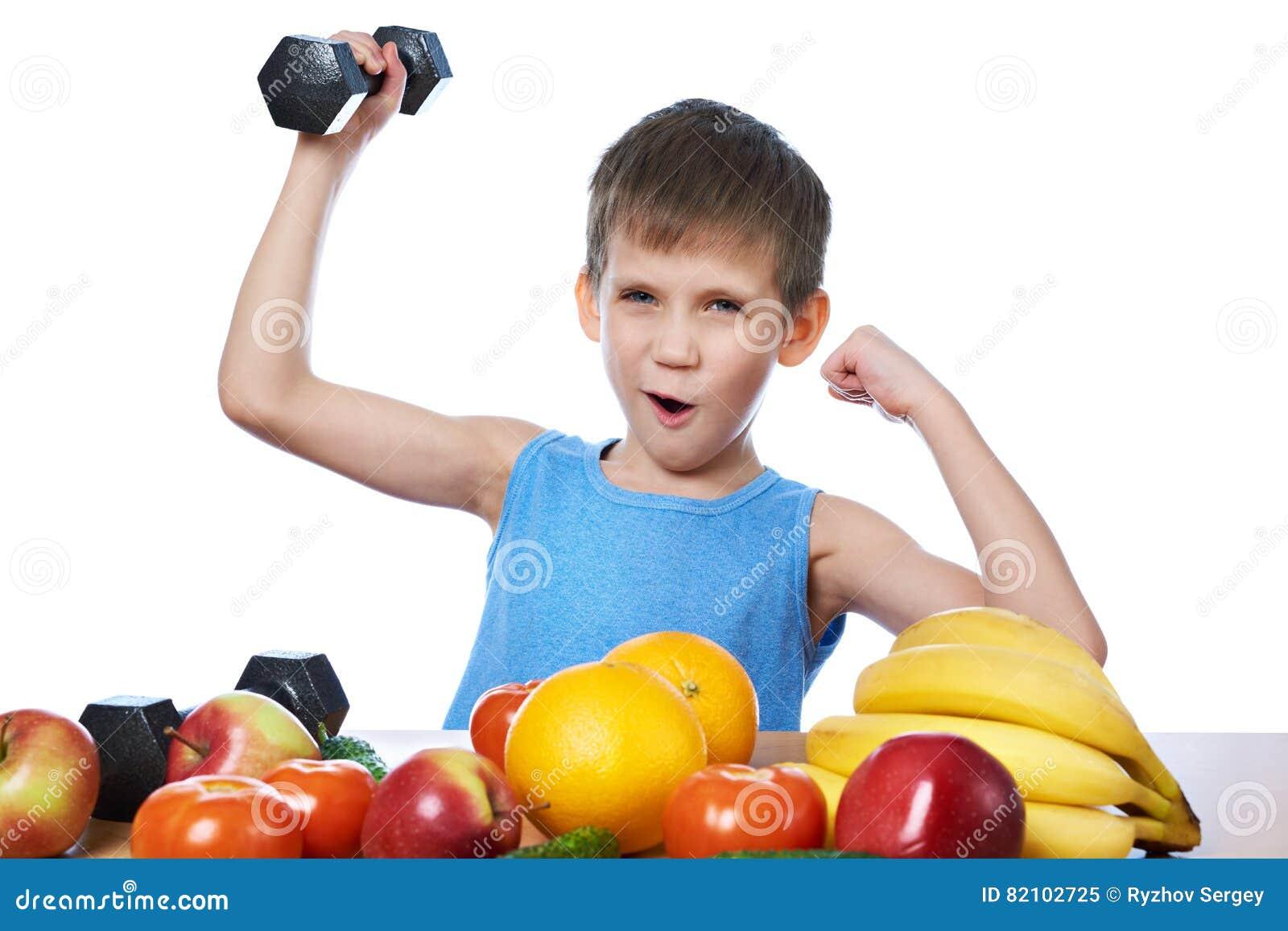 Muchacho deportivo sano con las frutas, las verduras y el aislante de las pesas de gimnasia