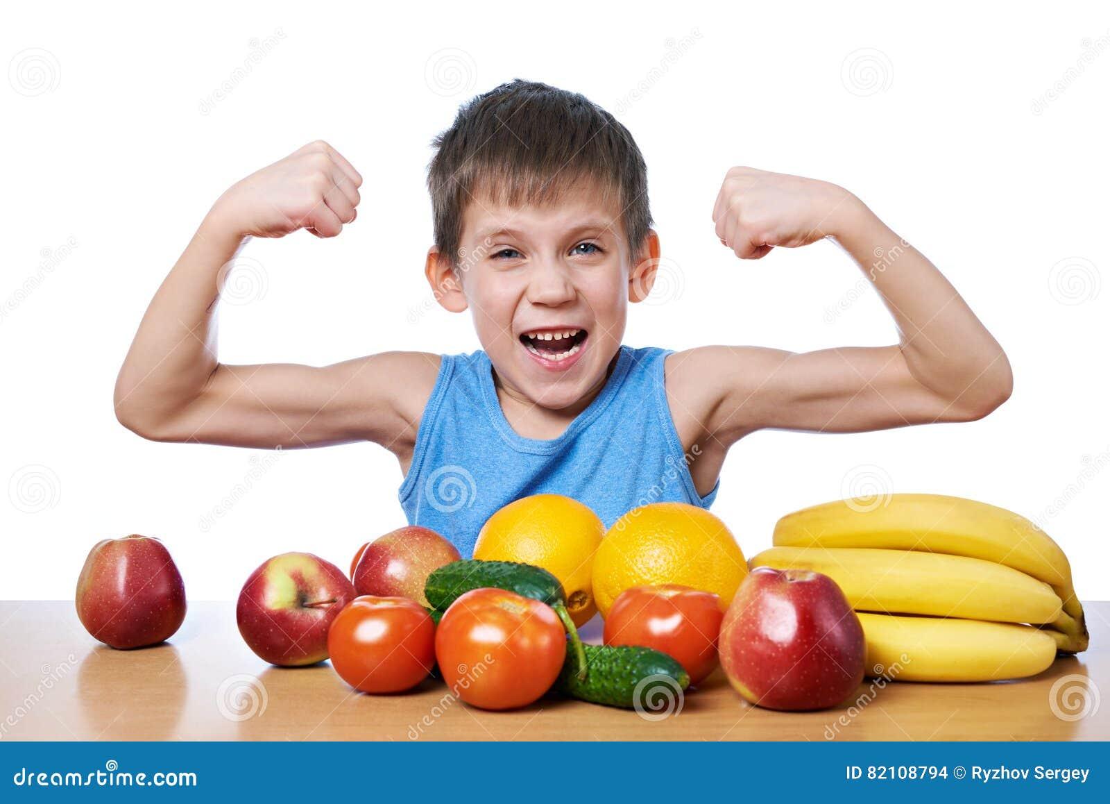 Muchacho deportivo sano con las frutas y verduras aisladas