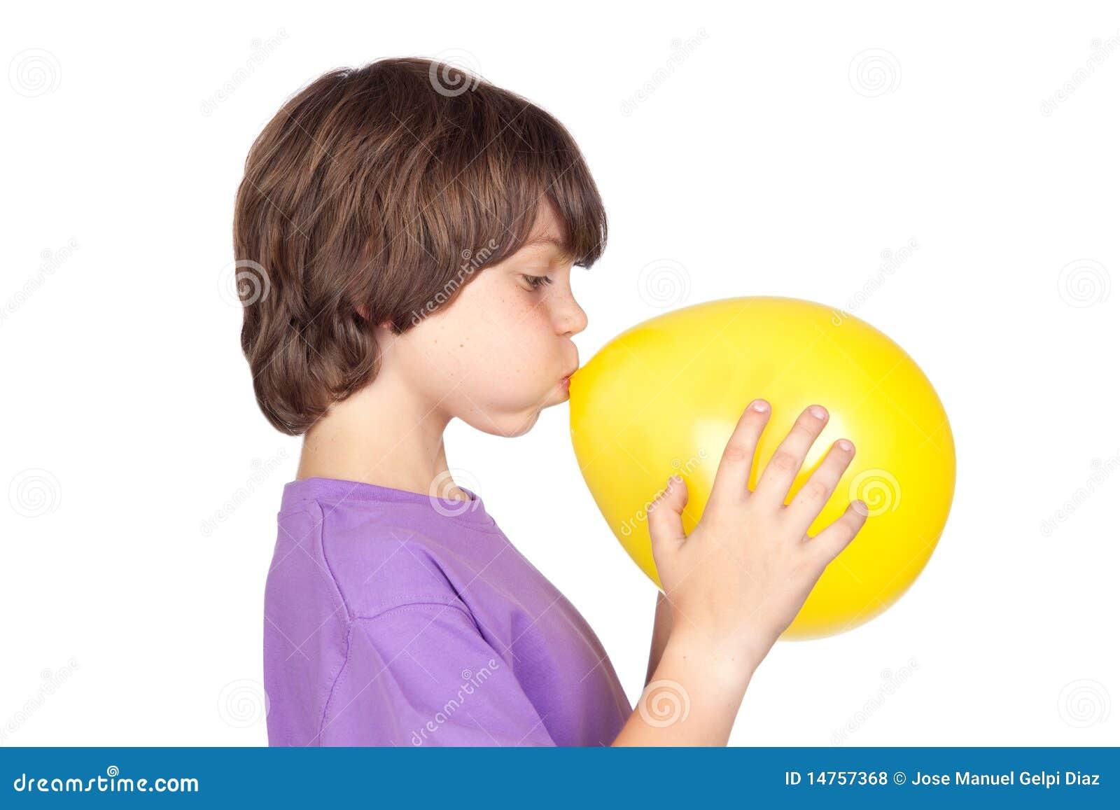 Muchacho divertido que hace saltar un globo amarillo