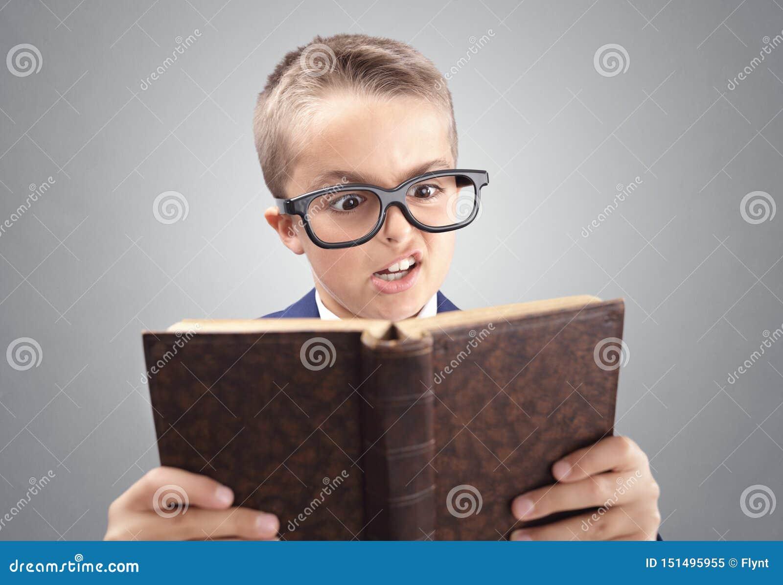 Muchacho ejecutivo joven chocado y sorprendido del hombre de negocios que lee un libro
