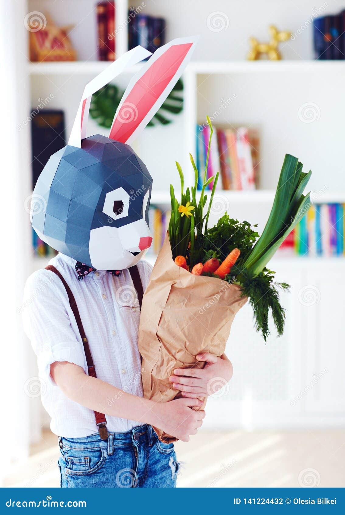 Muchacho elegante lindo, en máscara poligonal del conejo de pascua con un bolso por completo de los verdes frescos de la primaver