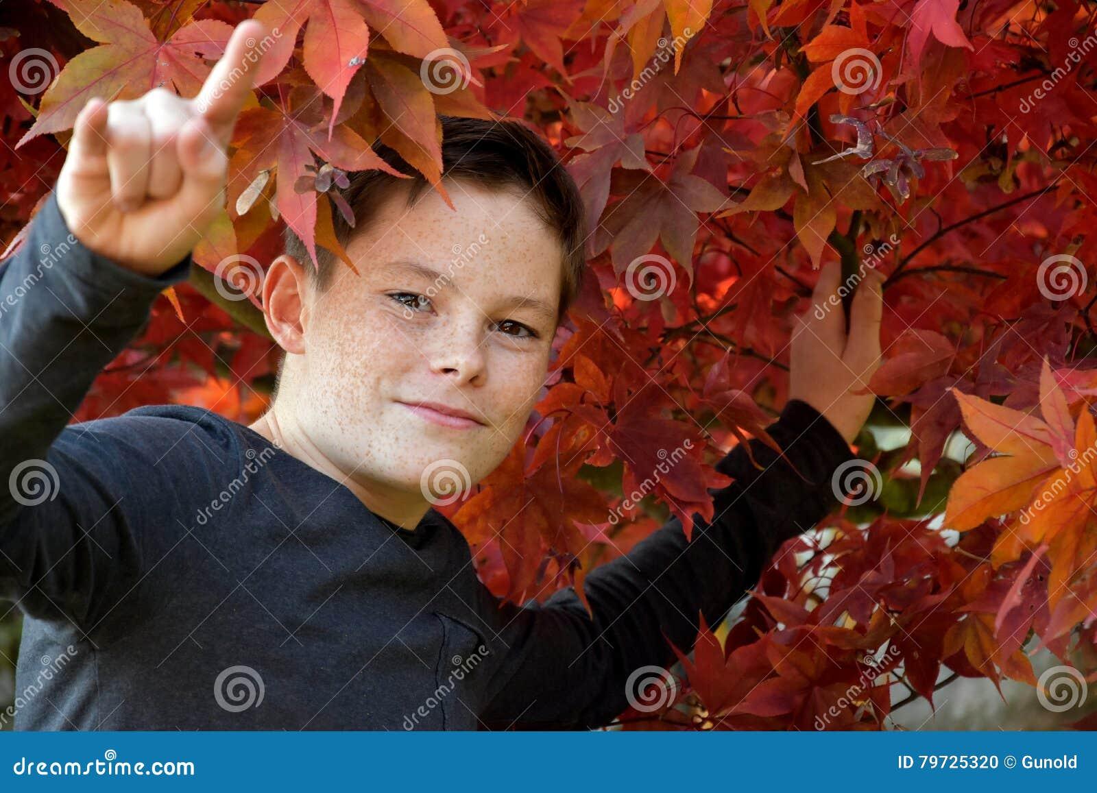 Muchacho en hojas de otoño