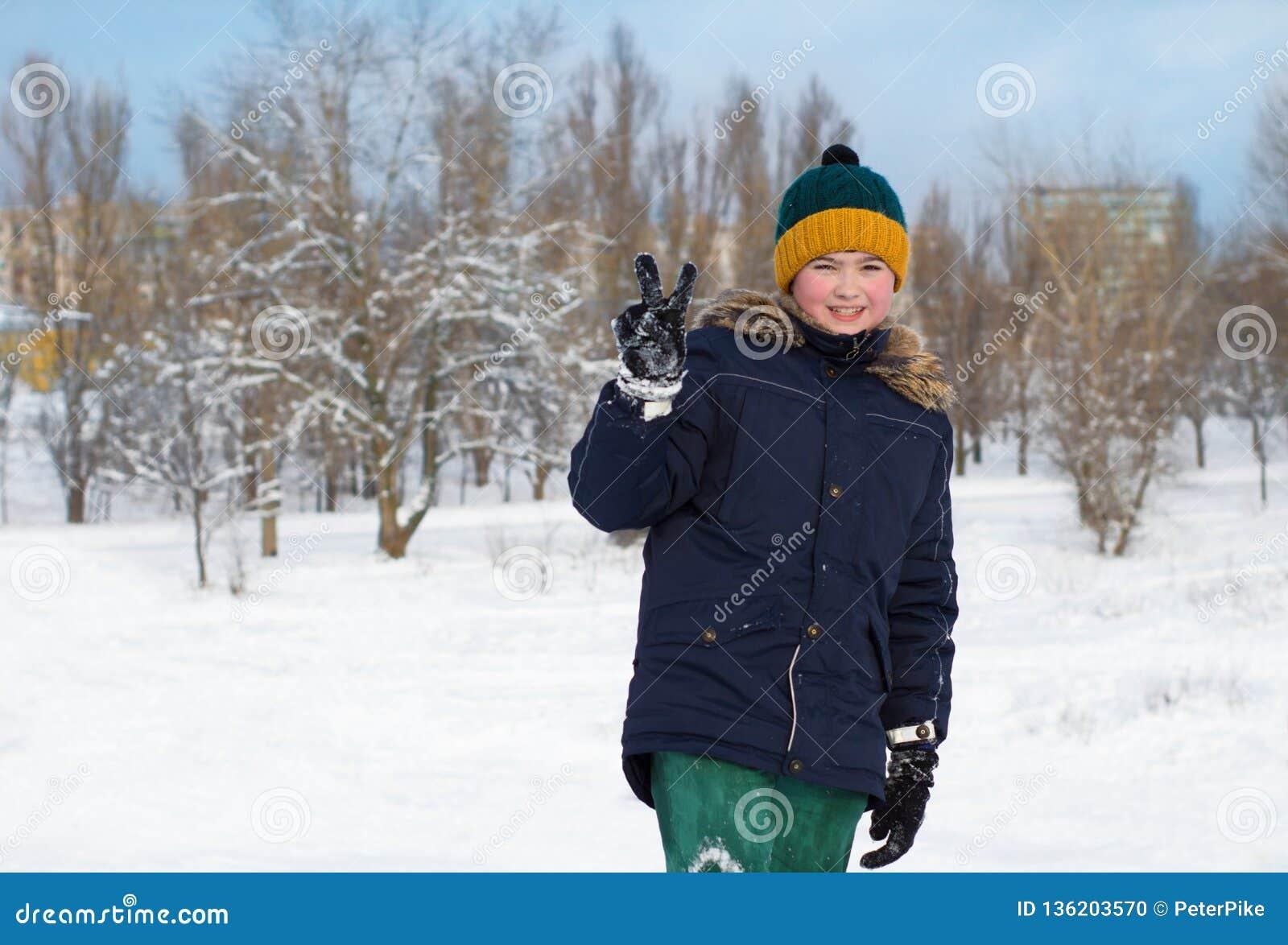 Muchacho en un sombrero con un bubón afuera en invierno