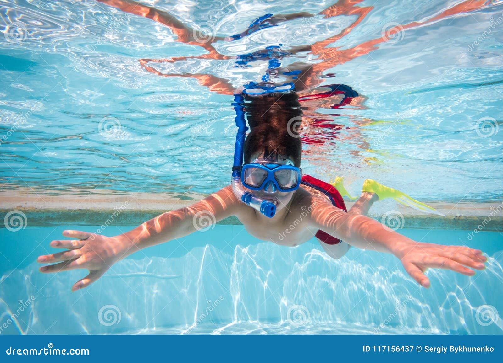 Muchacho en zambullida de la máscara en piscina