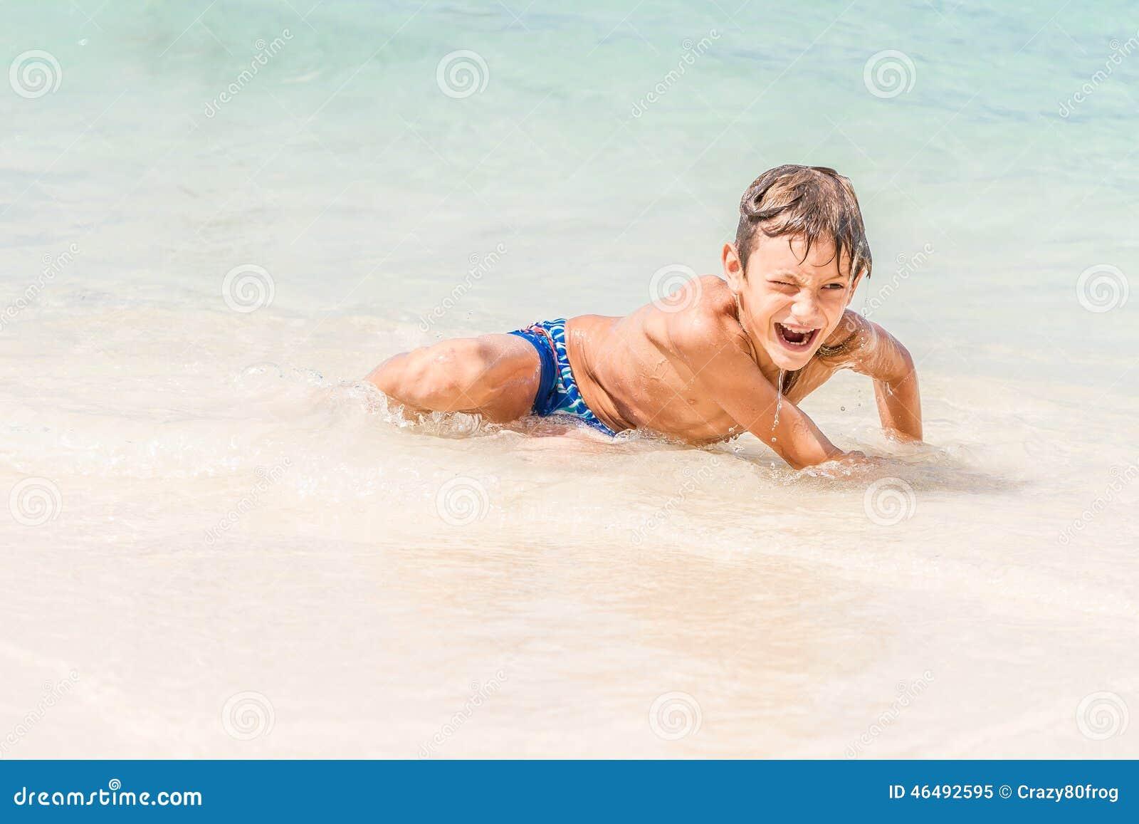 Muchacho feliz del niño que se divierte en el agua, vacat tropical del verano