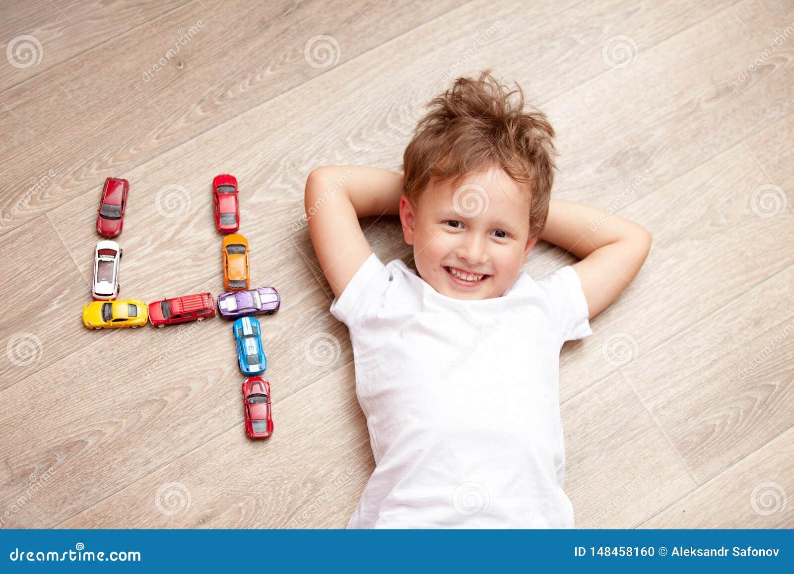 Muchacho feliz que juega en el piso con los juguetes