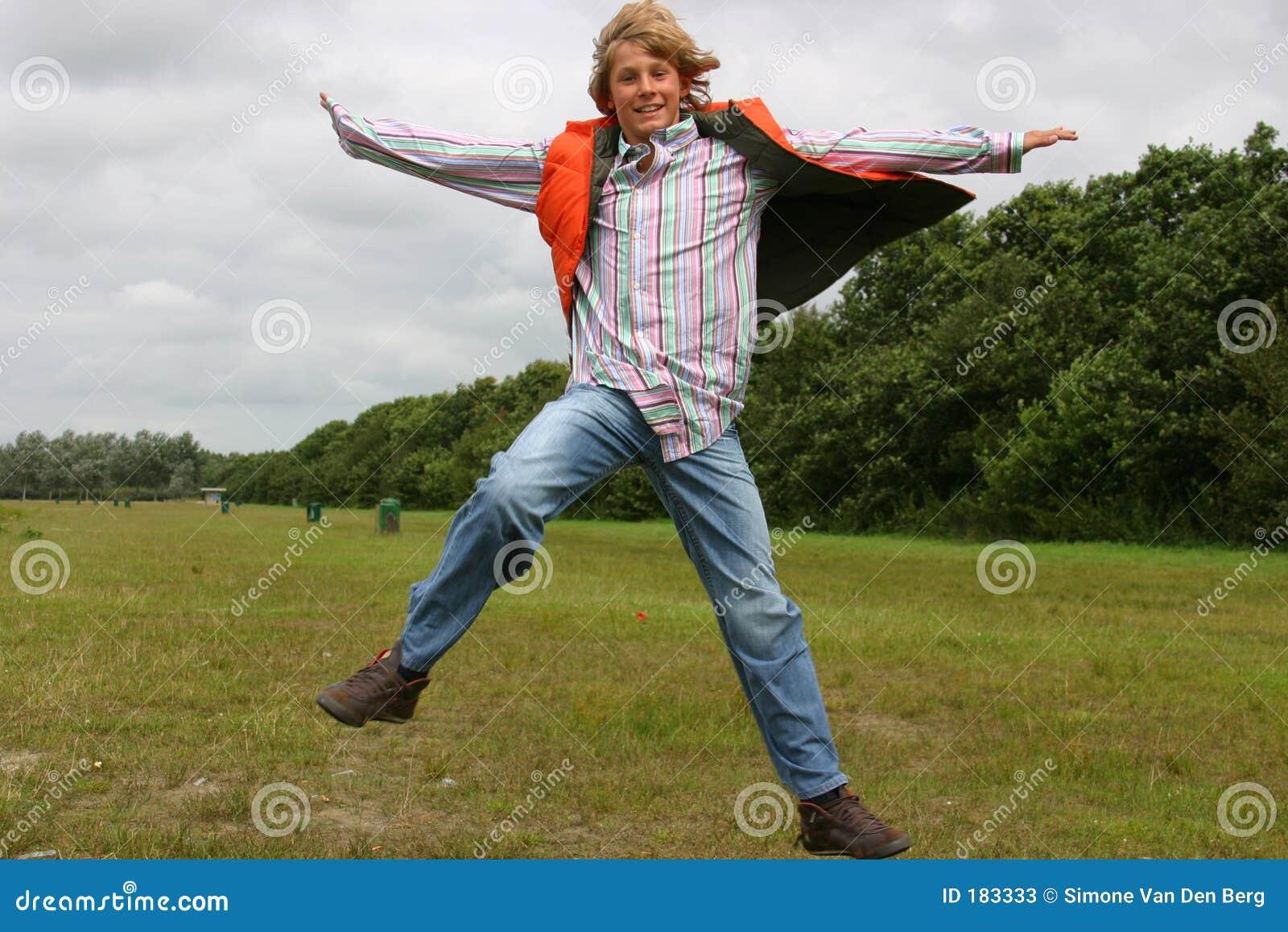 Muchacho feliz que salta para la alegría