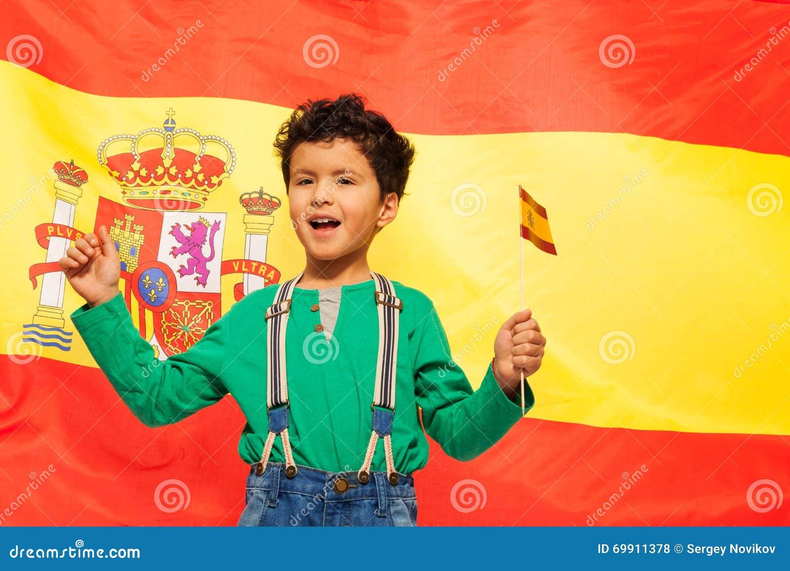 Muchacho hispánico feliz con la bandera española en su mano