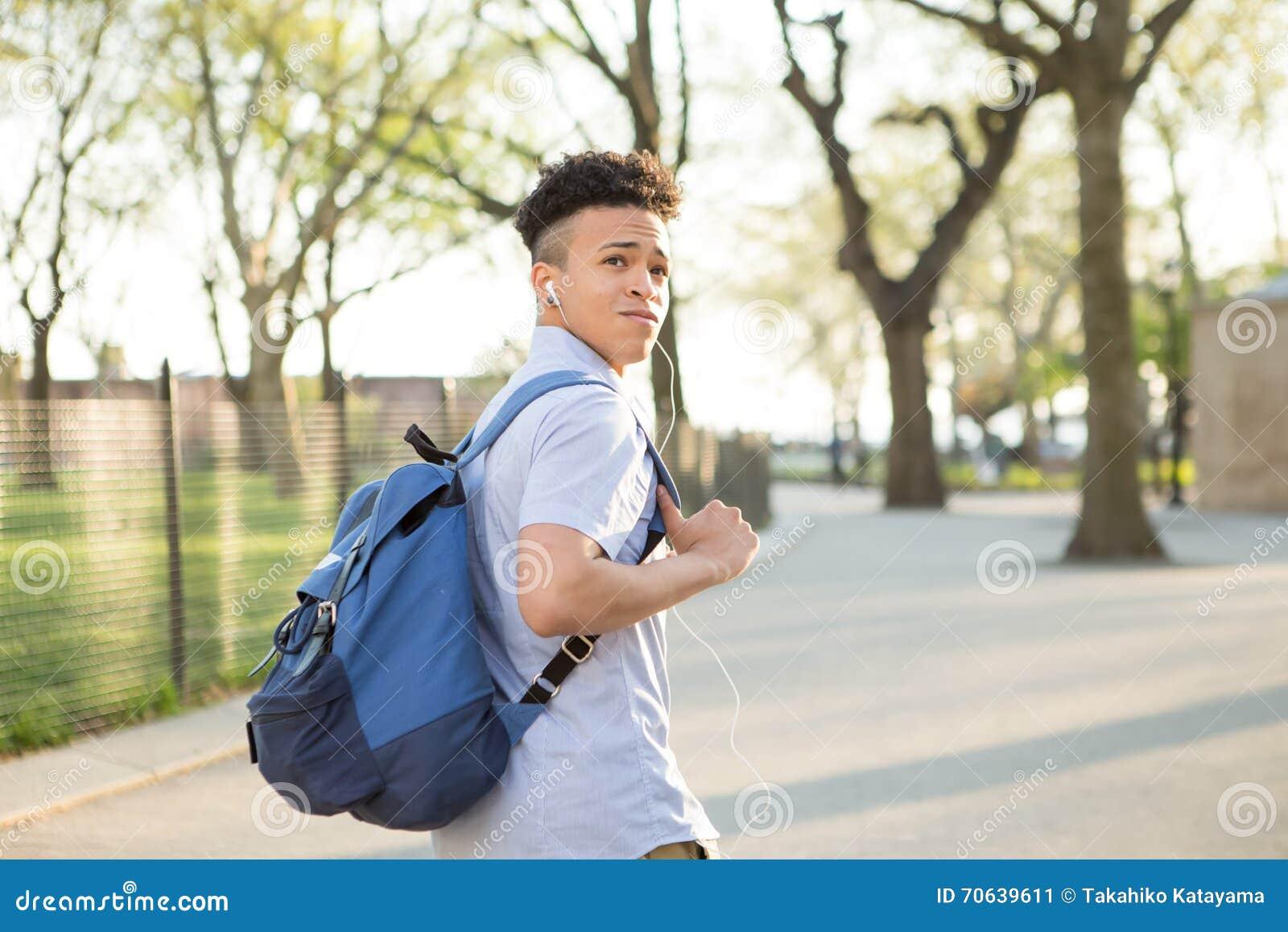 Muchacho hispánico joven con el paseo del packpack en campus de la universidad