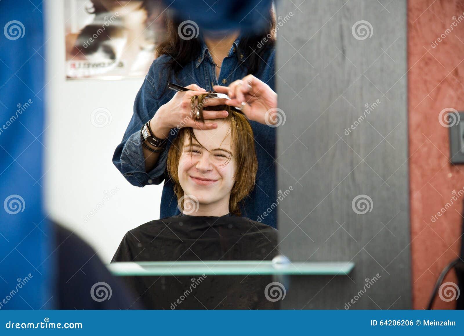 Muchacho joven con el pelo rojo en el peluquero