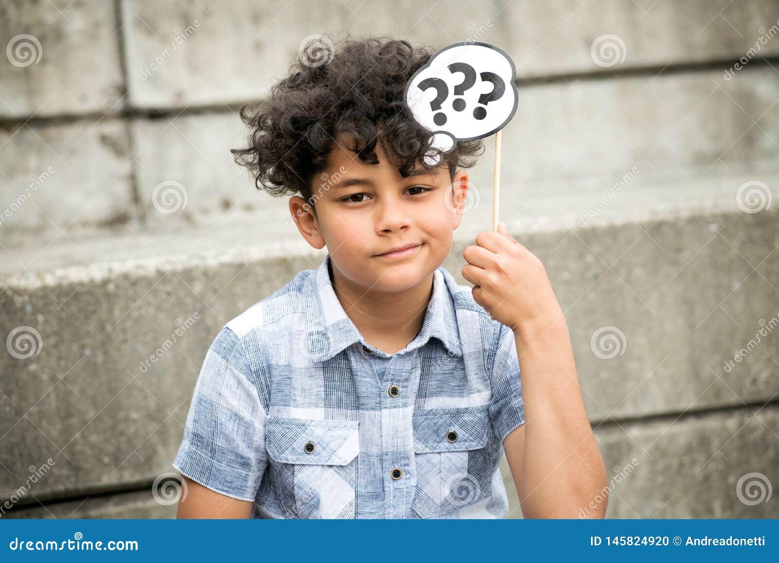 Muchacho joven confuso con los signos de interrogaci?n