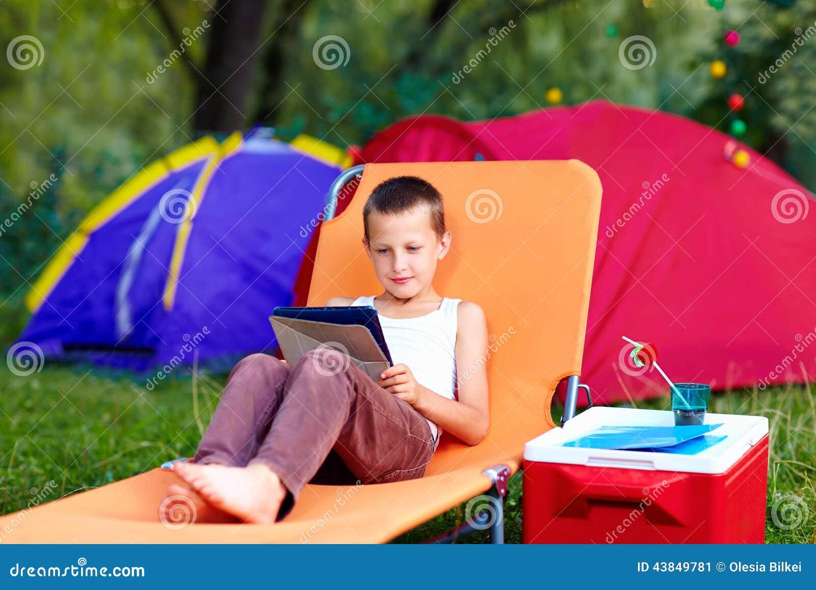 Muchacho joven en el campamento de verano, relajándose con la tableta