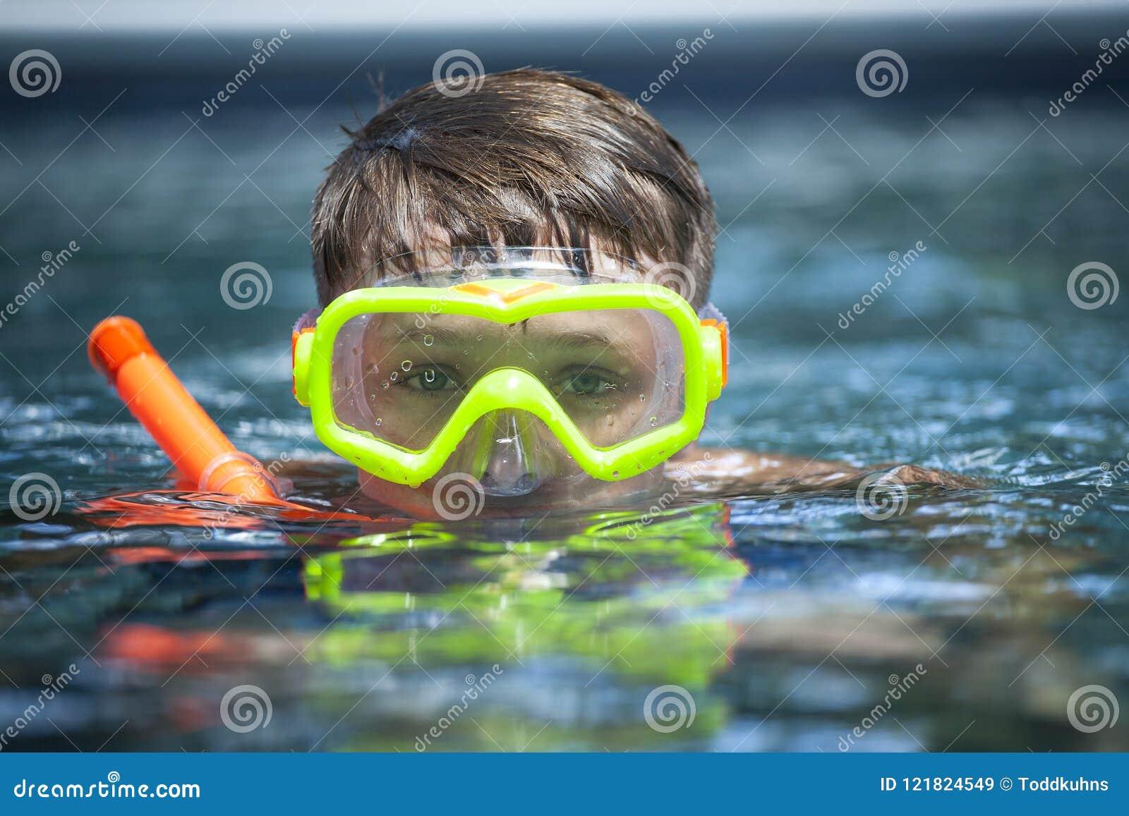 Muchacho joven en una piscina con una máscara del tubo respirador