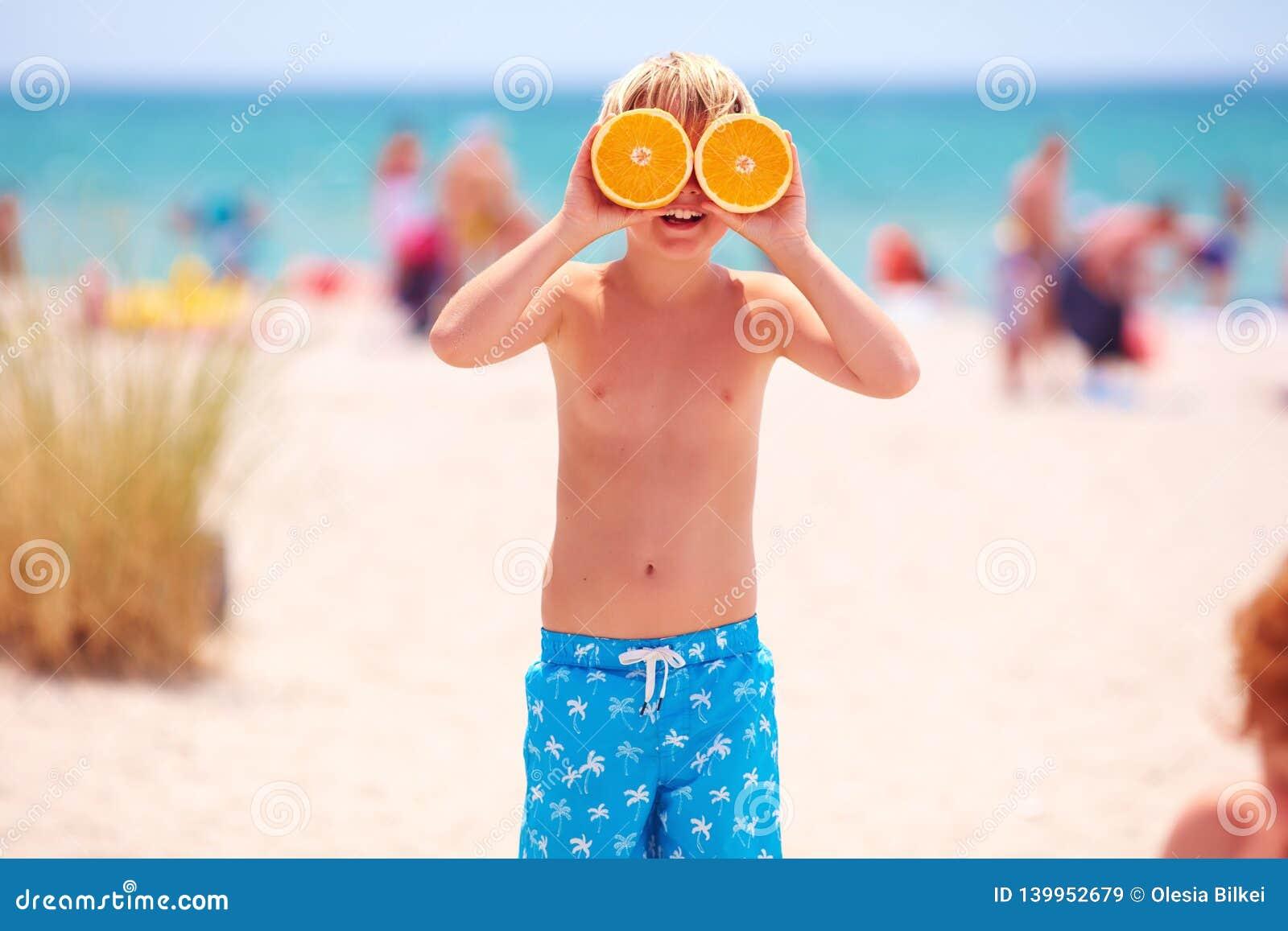 Muchacho joven feliz, niño con los ojos de la fruta cítrica en la playa arenosa durante vacaciones de verano