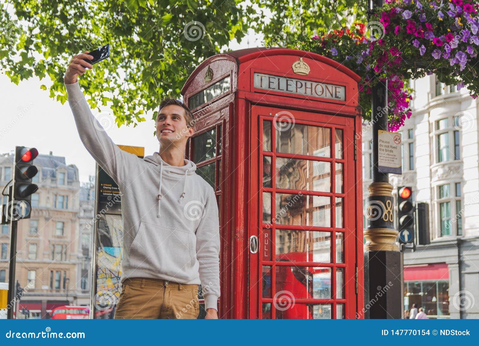 Muchacho joven feliz que toma un selfie delante de una caja del teléfono en Londond