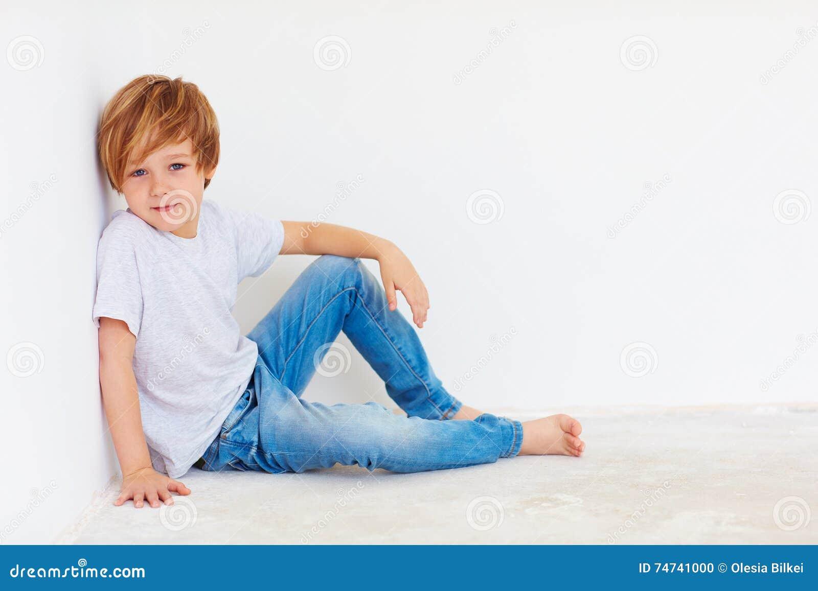 Muchacho joven hermoso, niño que se sienta cerca de la pared blanca