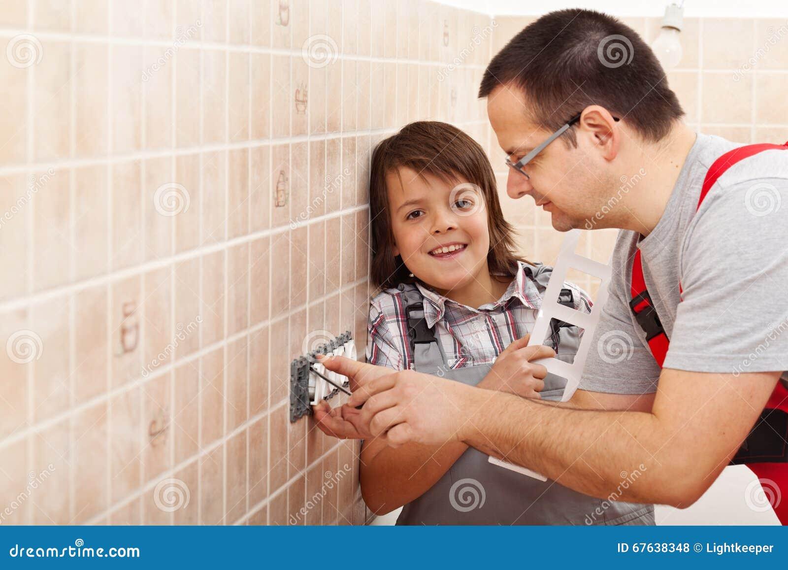 Muchacho joven que ayuda a su padre que instala el fixtur eléctrico de la pared
