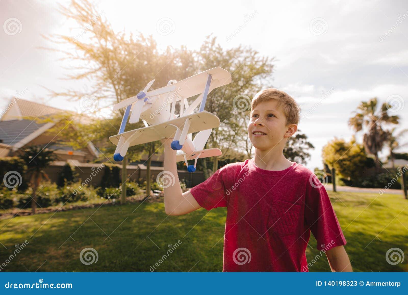 Muchacho joven que corre con un aeroplano del juguete