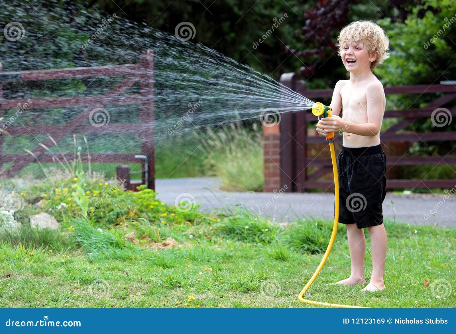 Muchacho joven que juega con la manguera y agua im genes for Manguera de agua