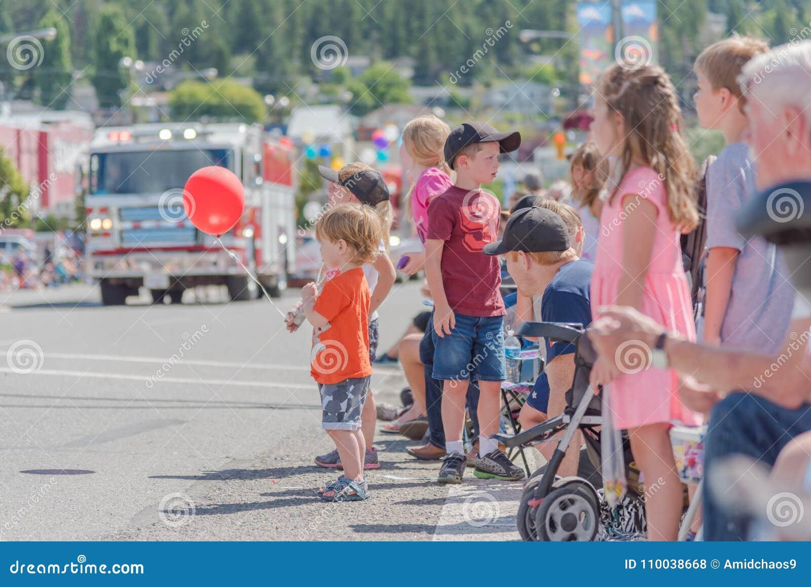 Muchacho joven que lleva a cabo el globo rojo con los niños y a los padres que miran desfile