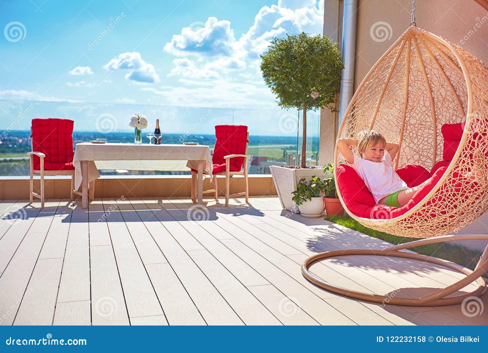 Muchacho joven que se relaja en hamaca en el patio moderno del tejado, terraza casera