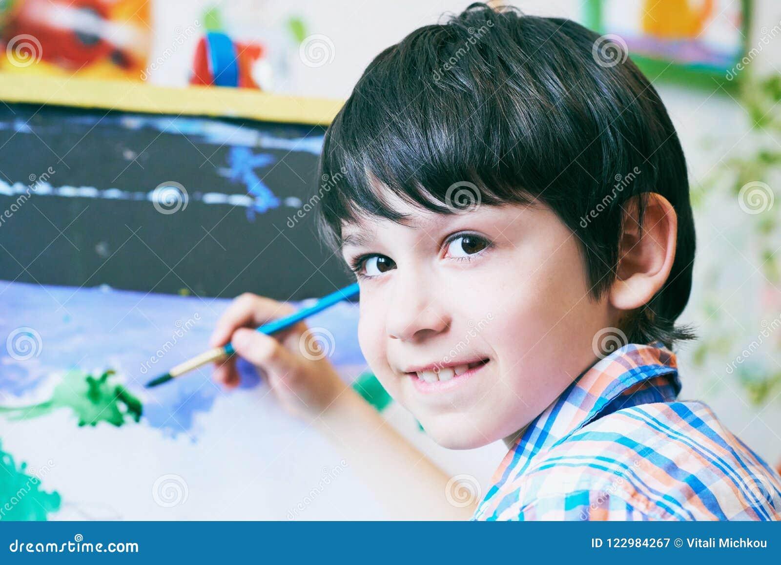 Muchacho joven que se sienta delante del caballete que pinta un pescado, sosteniendo un cepillo disponible y mirando en la sonris