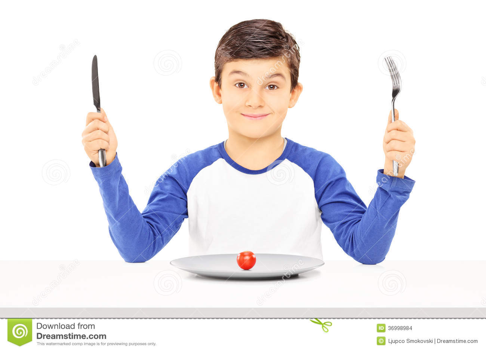 Muchacho joven que sostiene la bifurcación y el cuchillo con el tomate de cereza delante de