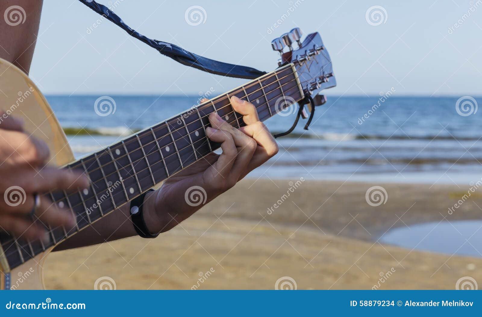 Muchacho joven que toca la guitarra acústica en la playa